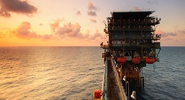 This is a picture of an offshore oil and gas platform at sunset with the orange, fading light reflecting off the water and represents petrochemical industry hair drug testing